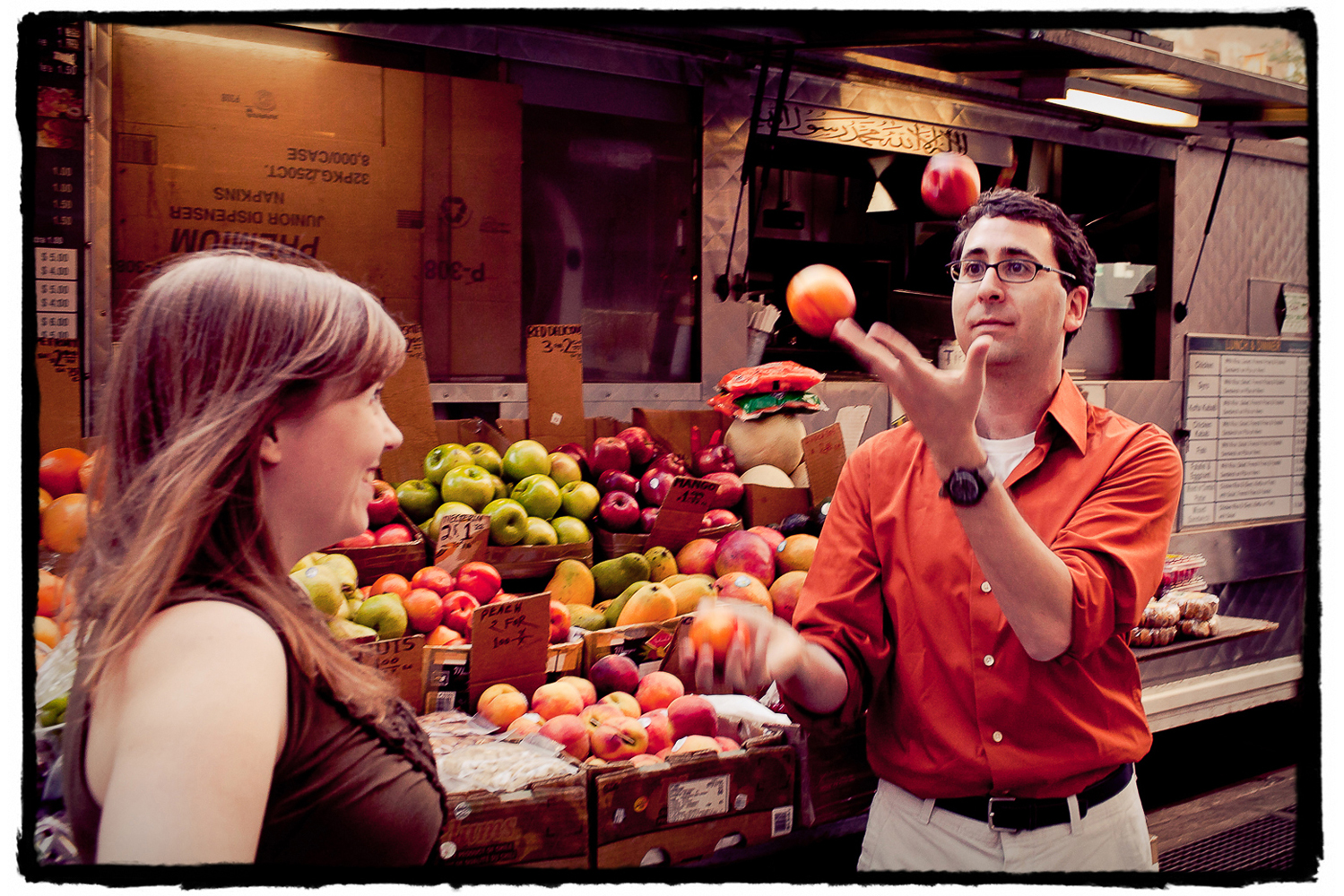 Engagement Portraits: Jason proves to Katie that he can in fact juggle at a fruit stand in manhattan.