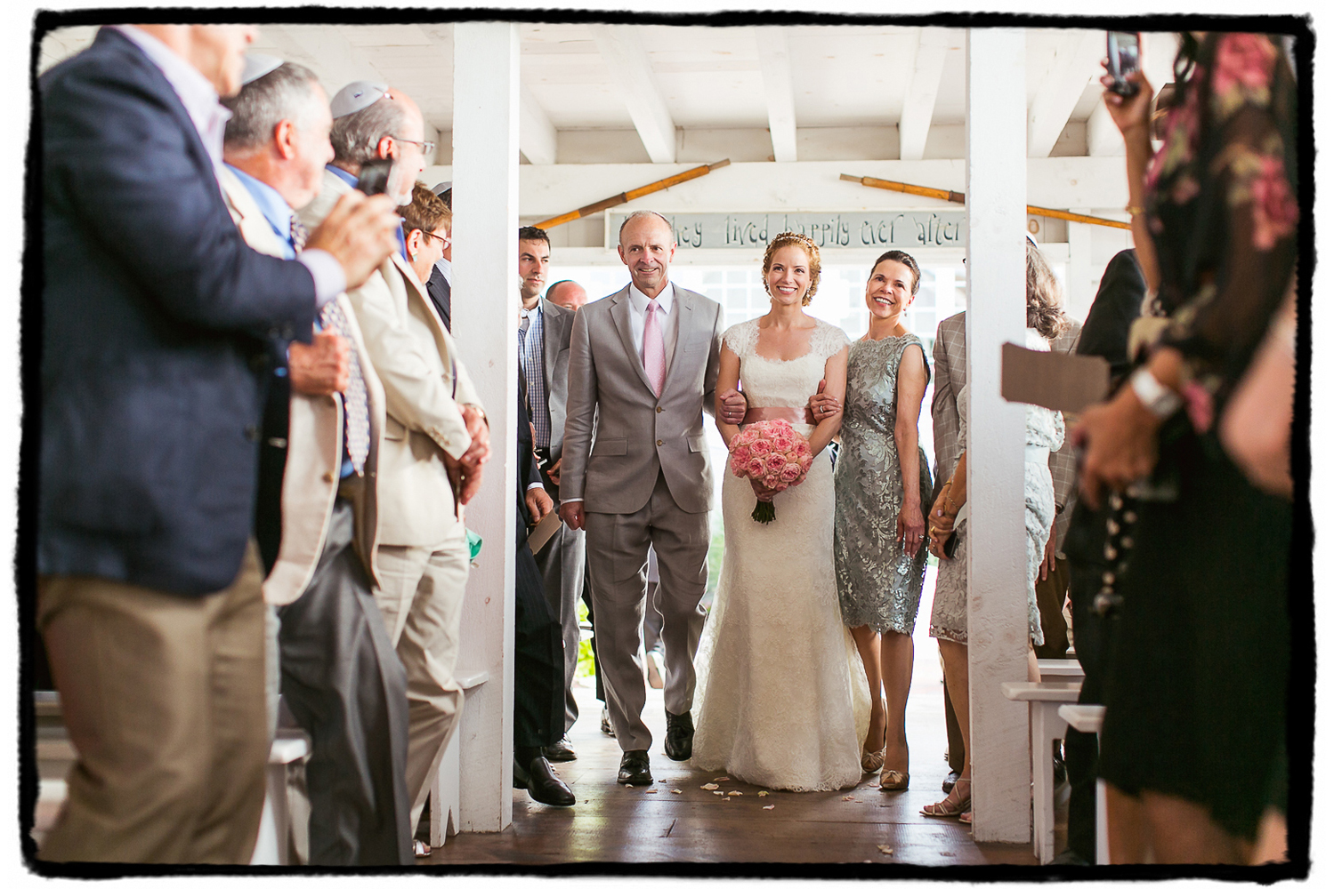Kelly is walked down the aisle by her parents in the seaside chapel at Bonnet Island Estate.