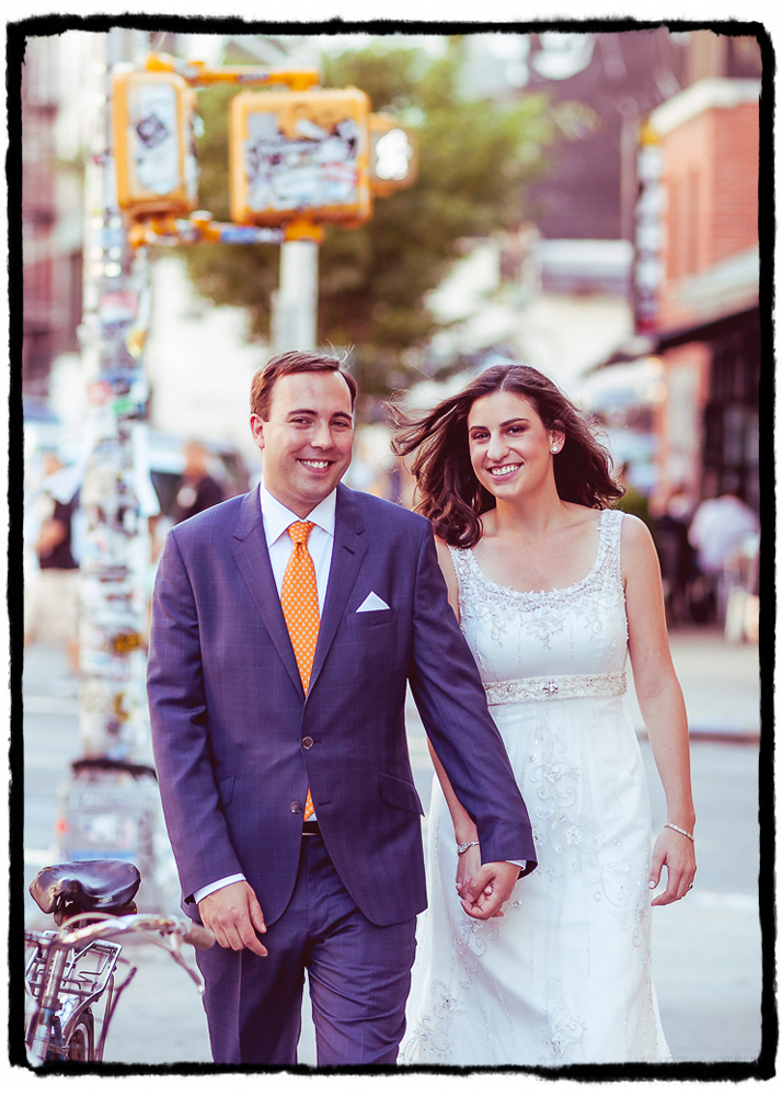 A simple shot of a couple walking down the city sidewalk in Soho on their wedding day.