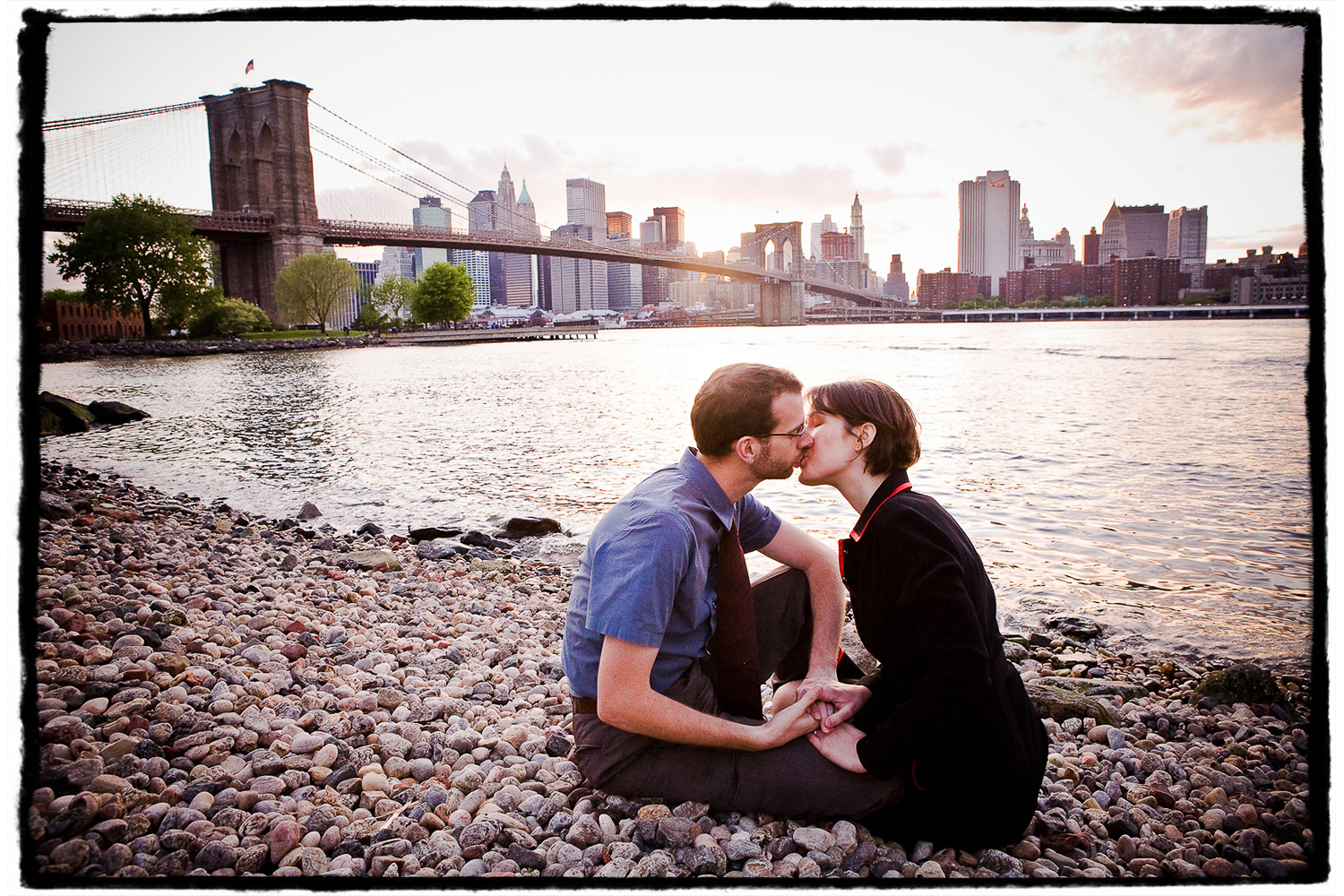 Engagement Portraits: Lindsay & Ben share a kiss on the pebbled beach in DUMBO, Brooklyn.