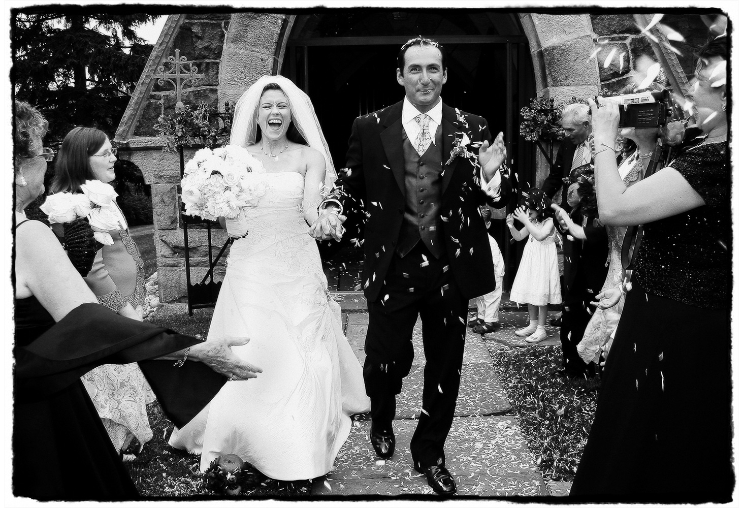 Guests cheer for the couple emerging from the small stone church after this summer ceremony in New Jersey.