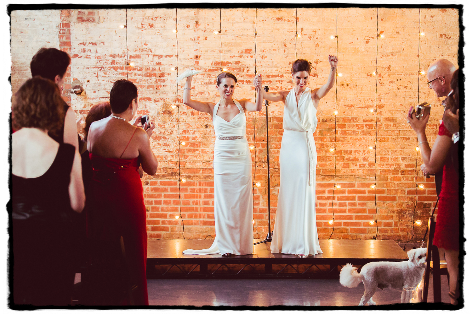 Lara & Nicole were married at The Green Building in front of a brick wall illuminated by hanging string lights.