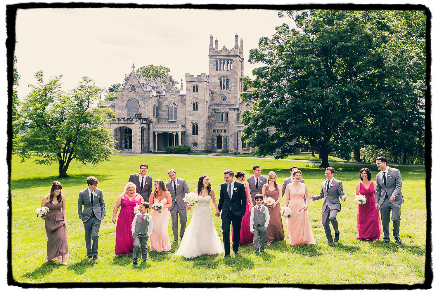 A wedding party in shades of pink and grey outside at Lyndhurst Castle in Westchester NY.