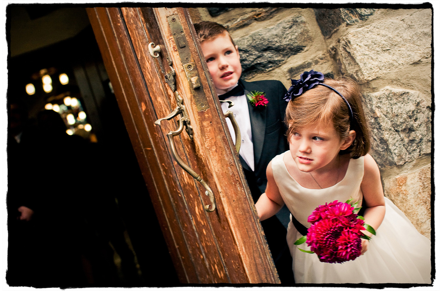 This flowergirl and ring bearer hold the door as adults stream out of the church after a lovely ceremony preceding a reception at The Garrison.