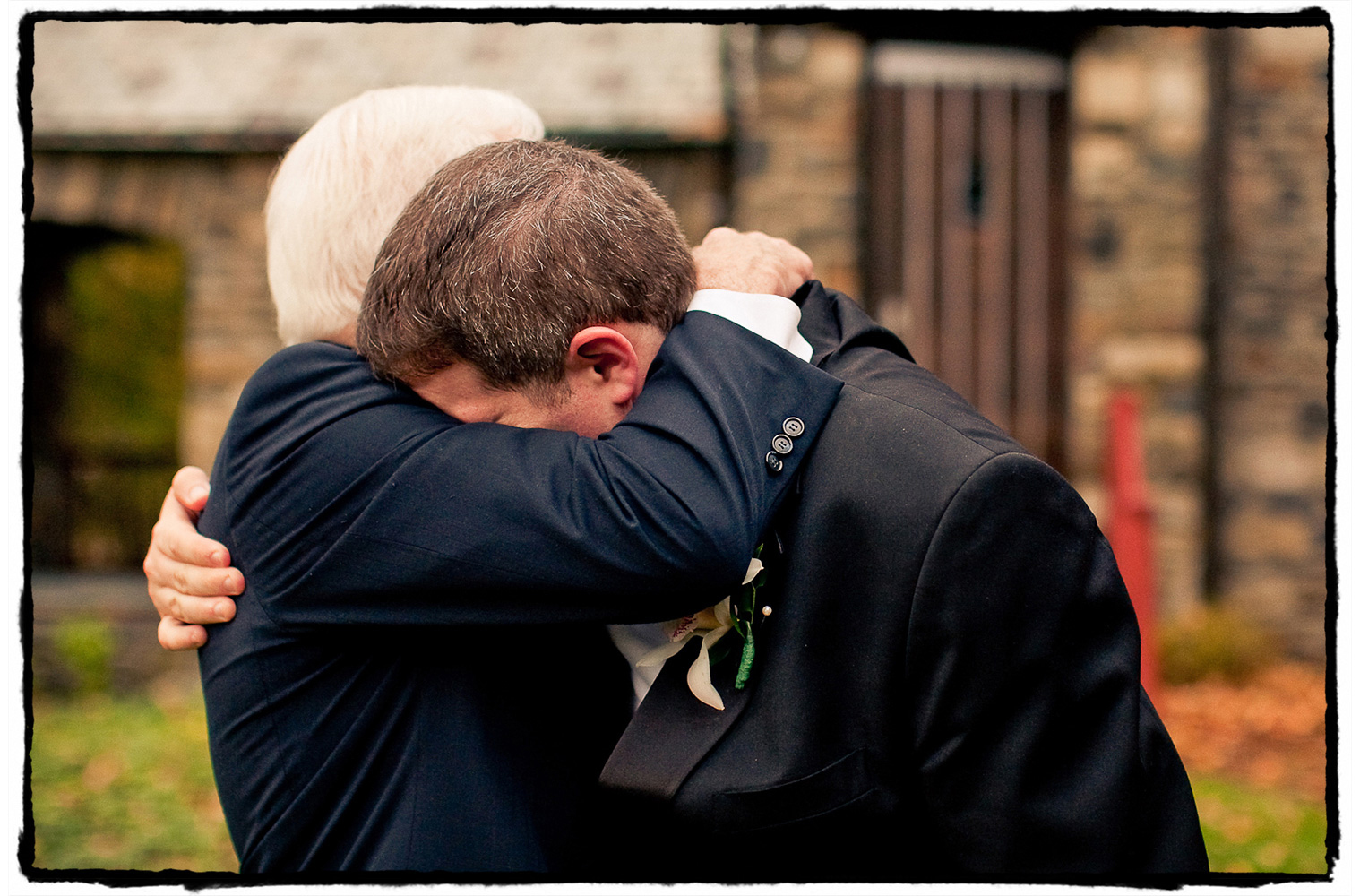This groom shares an emotional hug with his father after marrying the love of his life.