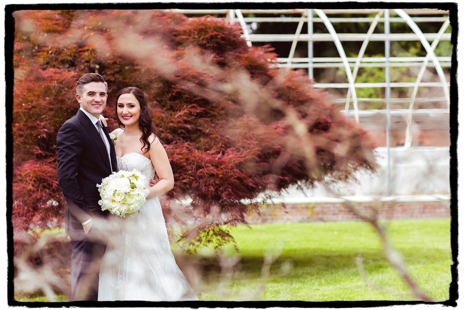 I love shooting through foliage, or in this case creating a nice blurry bokeh in the foreground wtih some branches framing the couple on the left.  The red maple behind them makes them pop and I loved the graphic lines in the greenhouse to the right.