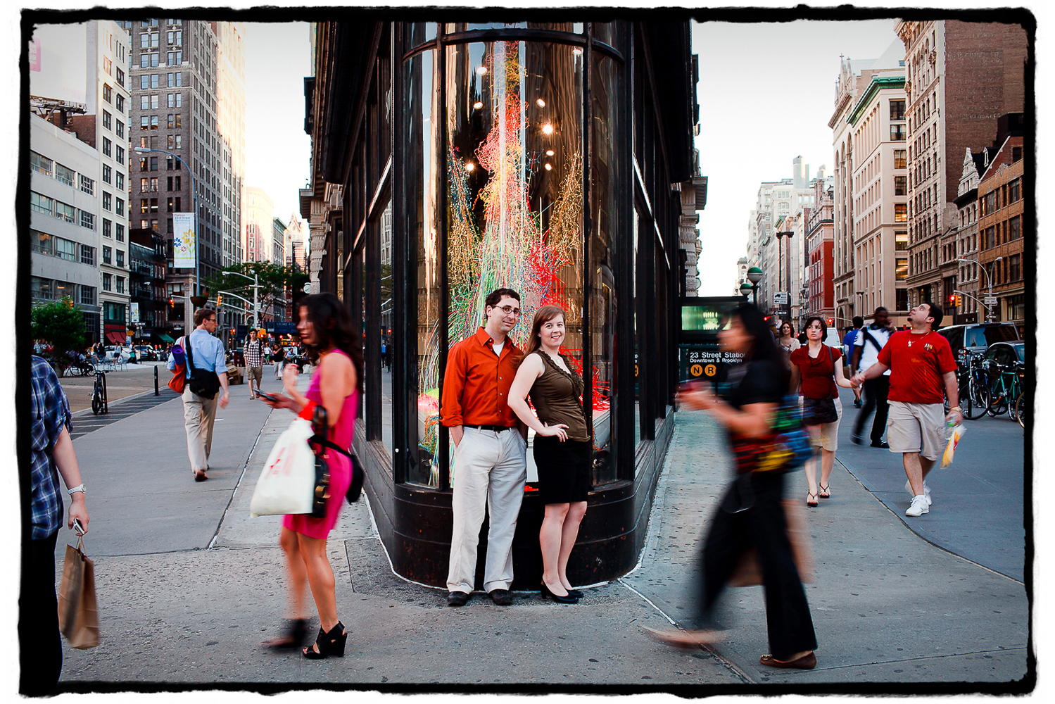 Engagement Portrait: Katie & Jason stop to take in the action in front of NYC's Flatiron Building.